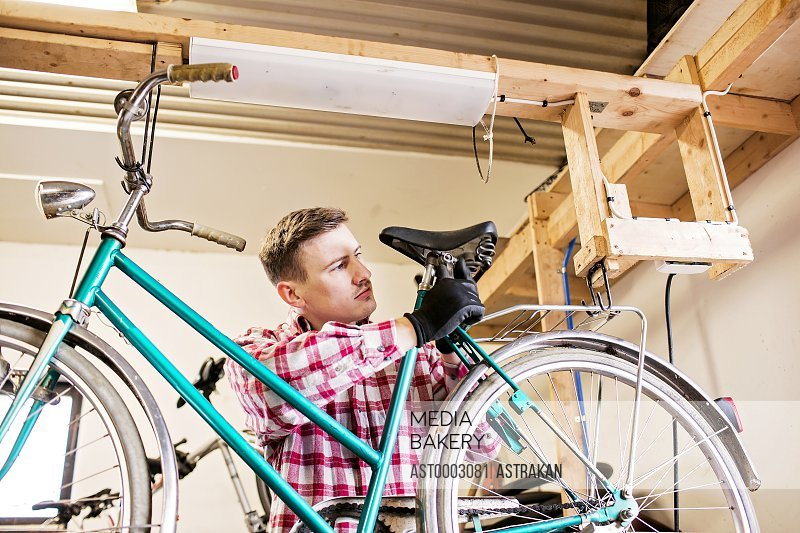 Mid adult repairman fixing bicycle seat in workshop