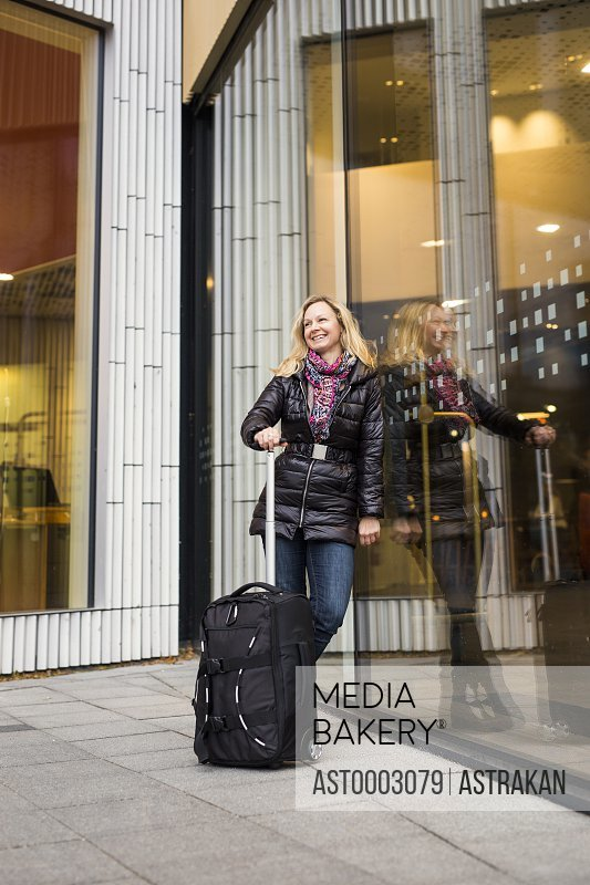 Happy businesswoman with luggage standing at hotel entrance
