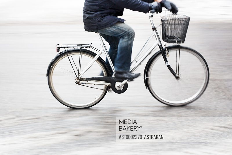 Side view low section of man riding bicycle on snow covered street