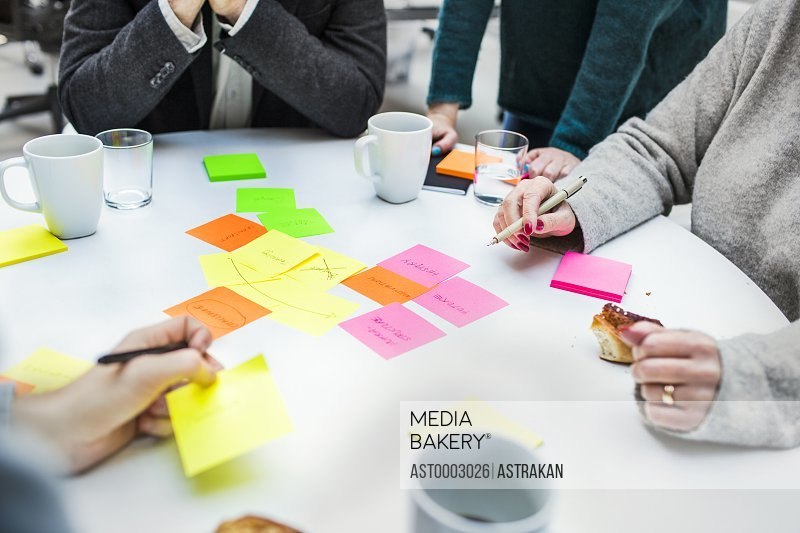 Cropped image of business people with adhesive notes at table in creative office