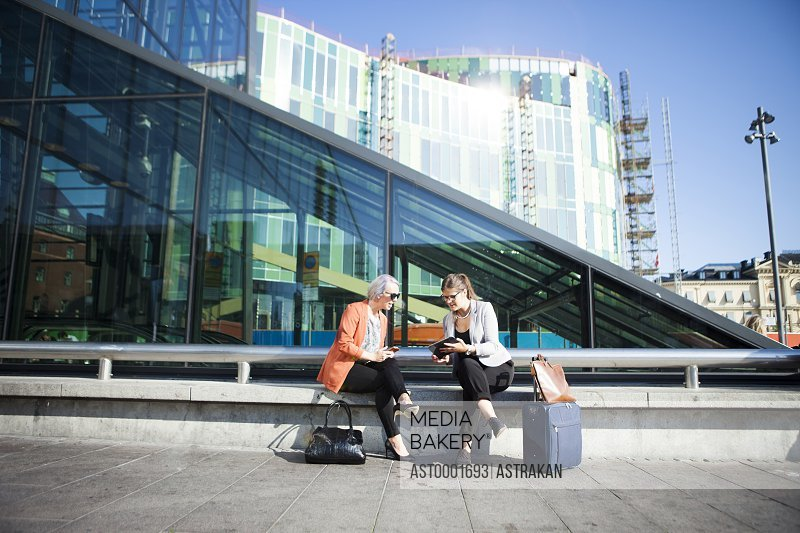Businesswomen discussing over digital tablet while sitting on retaining wall outside railroad station