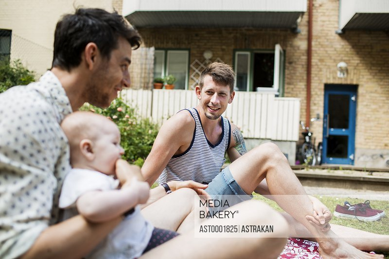 Gay couple sitting with baby girl at yard