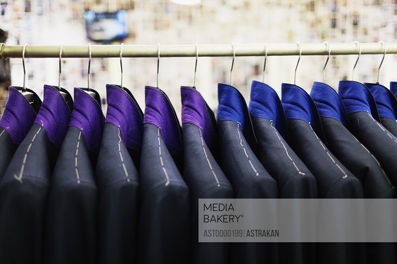 Close-up of suits hanging on rack in designer showroom