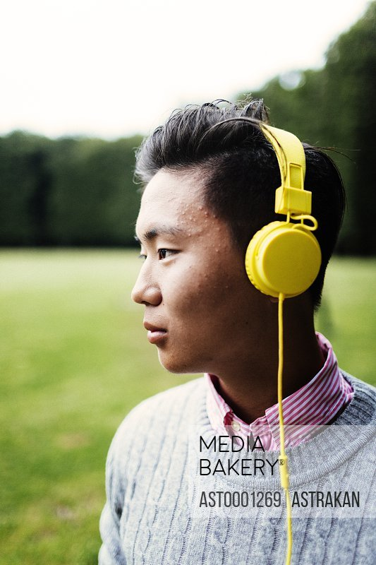 Young man looking away while listening music at park