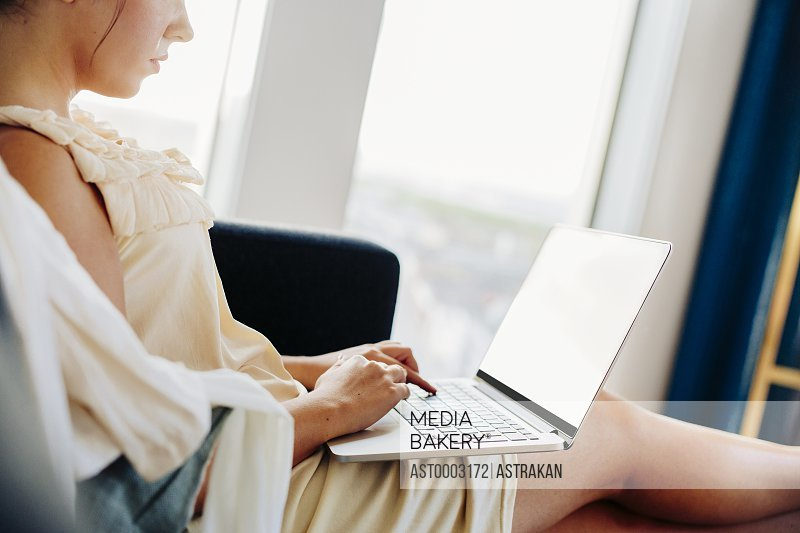 Midsection of woman typing on laptop while sitting on sofa at hotel