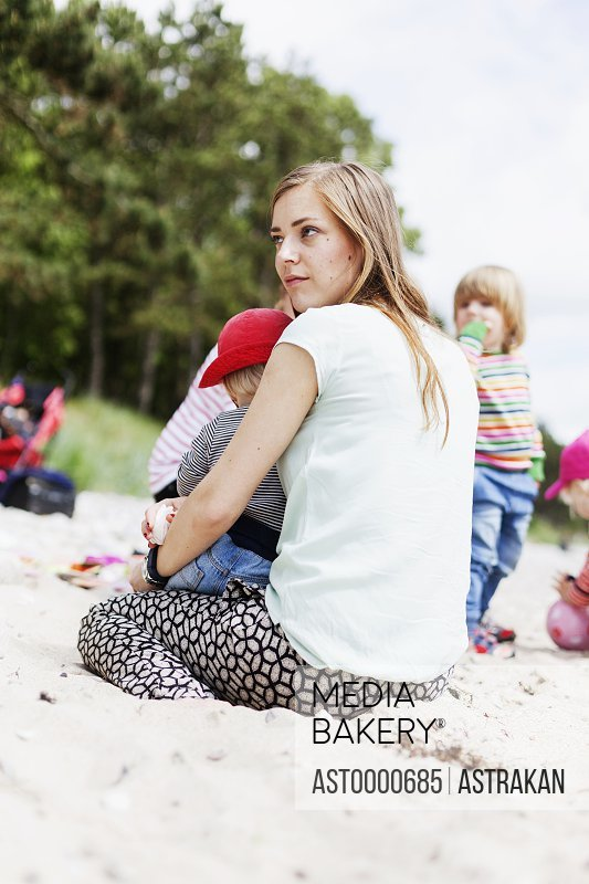 Woman sitting with baby boy on sand at beach