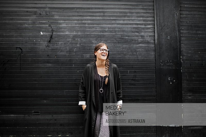 Happy woman looking away while standing against black shutter
