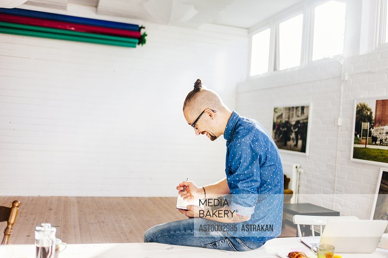 Smiling mid adult businessman writing in diary at creative office