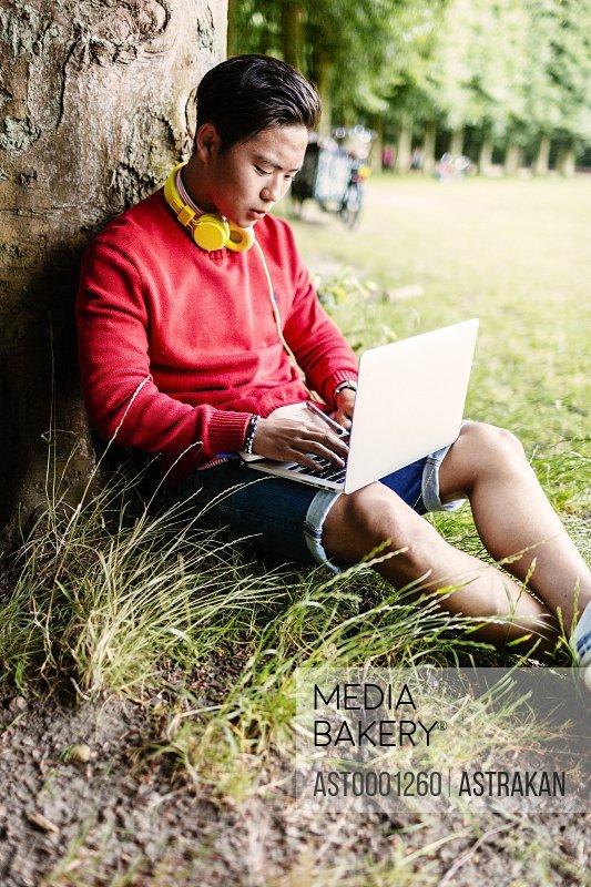 Male university student using laptop at park