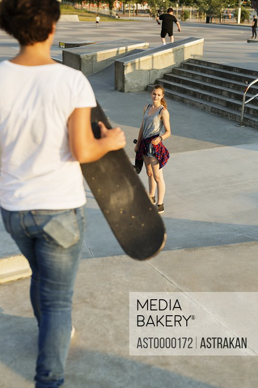 High angle view of teenage girl looking at female friend in skate park