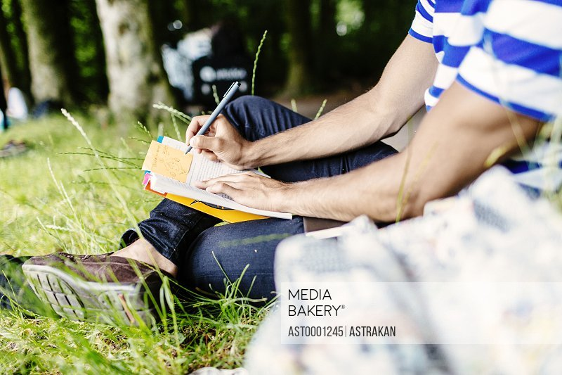 Low section of man writing in book while studying at park
