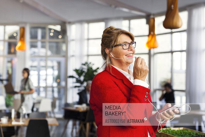 Happy businesswoman talking through earphone while standing in restaurant