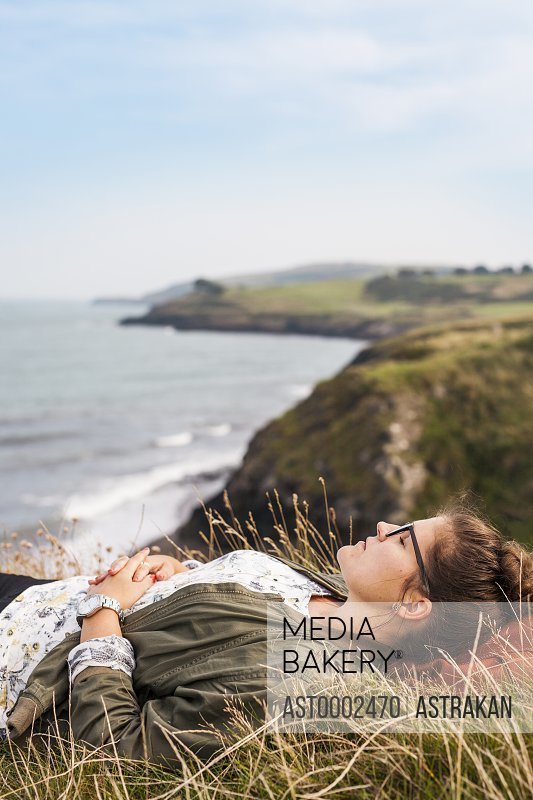 Side view of woman sleeping on grassy hill by sea