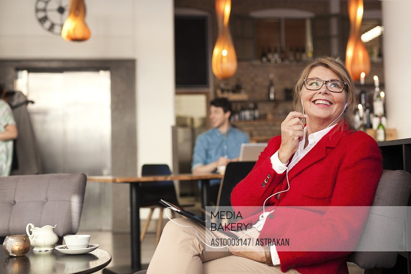 Businesswoman talking through earphones while sitting at restaurant