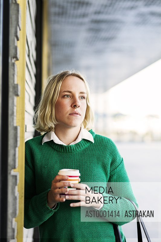 Young woman holding coffee cup while looking away outdoors