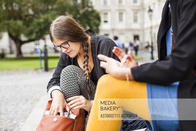 Woman searching something in bag while sitting with friend on steps