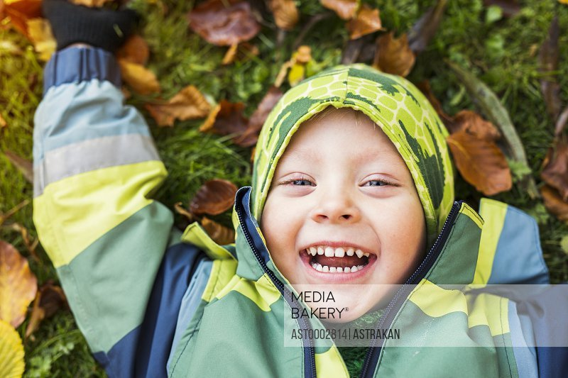 Portrait of cheerful boy lying on ground in forest during autumn