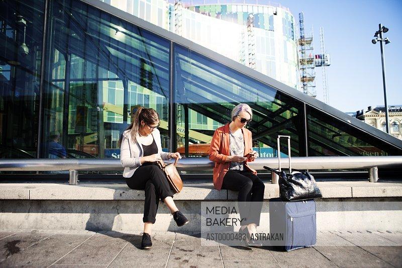Businesswomen sitting on retaining wall outside railroad station