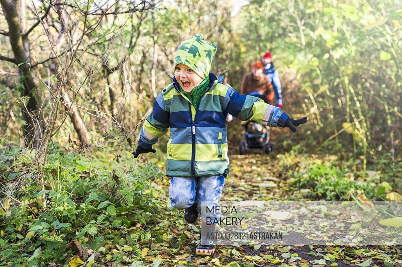 Full length of excited boy running with arms outstretched in forest