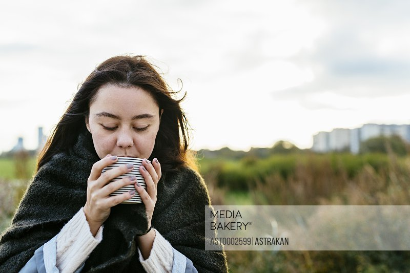 Young woman drinking coffee on beach against sky