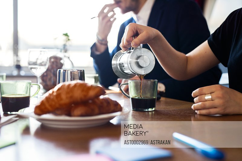 Cropped image of businesswoman poring coffee into cup at table in office