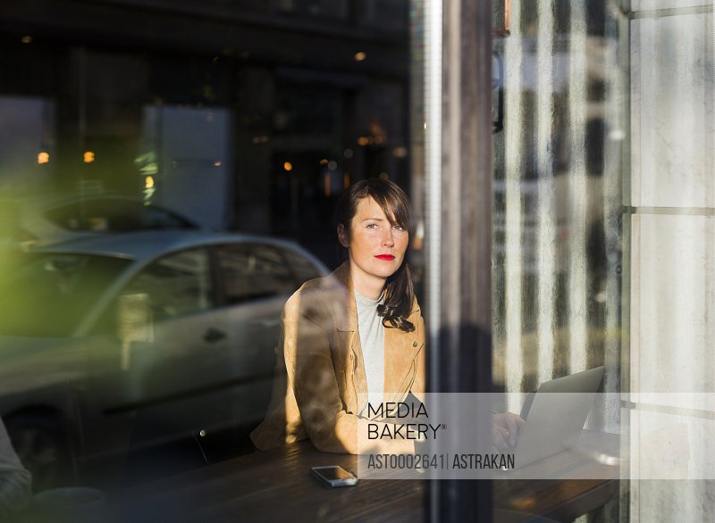 Thoughtful woman looking through window while using laptop in cafe