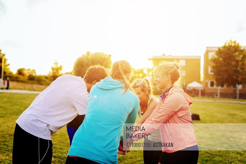 Sporty friends stacking hands in huddle at park during sunset