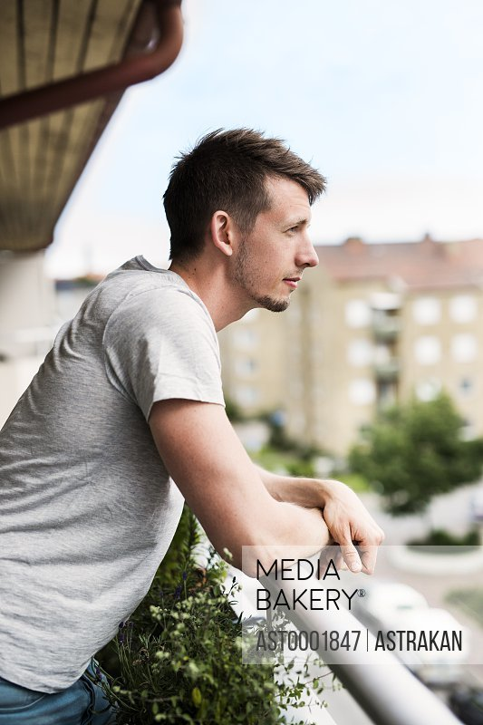 Side view of thoughtful man leaning on balcony