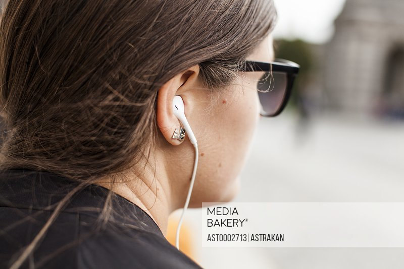 Close-up rear view of woman looking away while listening music outdoors