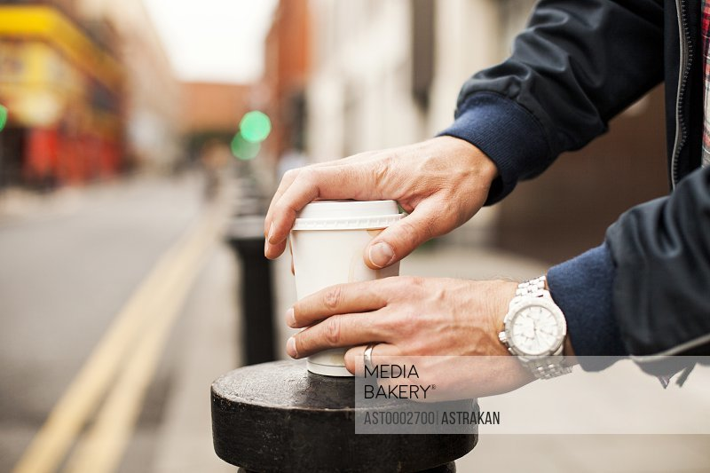 Midsection of man opening disposable cup on bollard at sidewalk