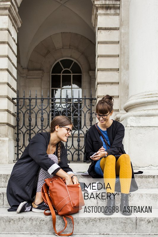 Happy female friends using smart phone while sitting on steps outside building