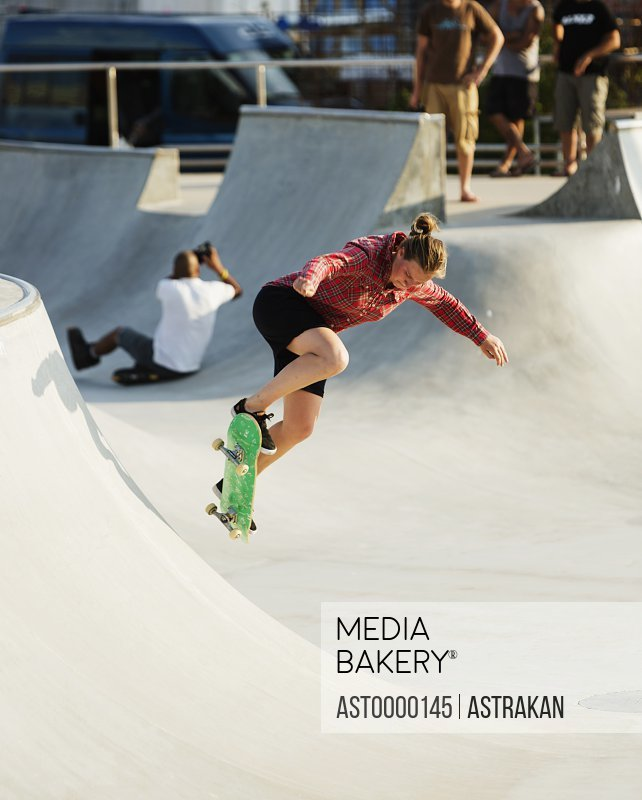 Full length of sporty woman performing stunt on ramp in city skate park