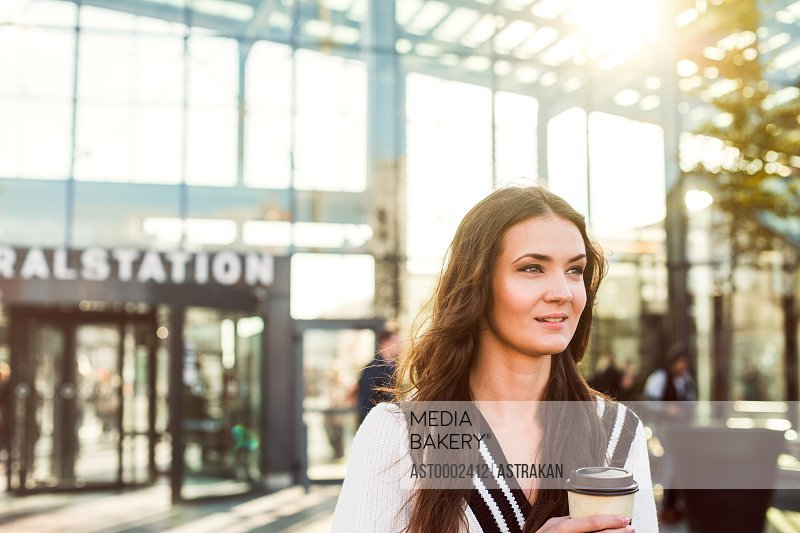 Beautiful businesswoman holding disposable cup outside railroad station