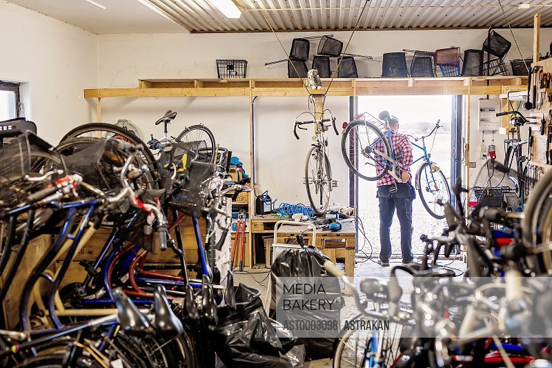 Rear view of repairman carrying bicycle at doorway of workshop