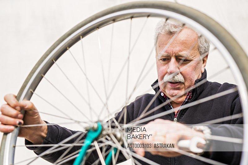 Senior man tightening bicycle tire outside workshop
