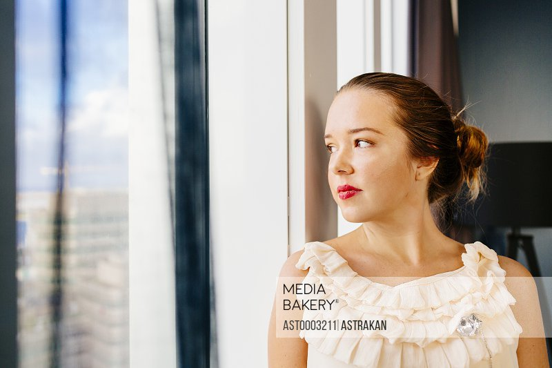 Thoughtful woman standing by window at hotel room