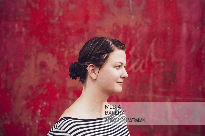 Thoughtful woman standing against red wall outdoors