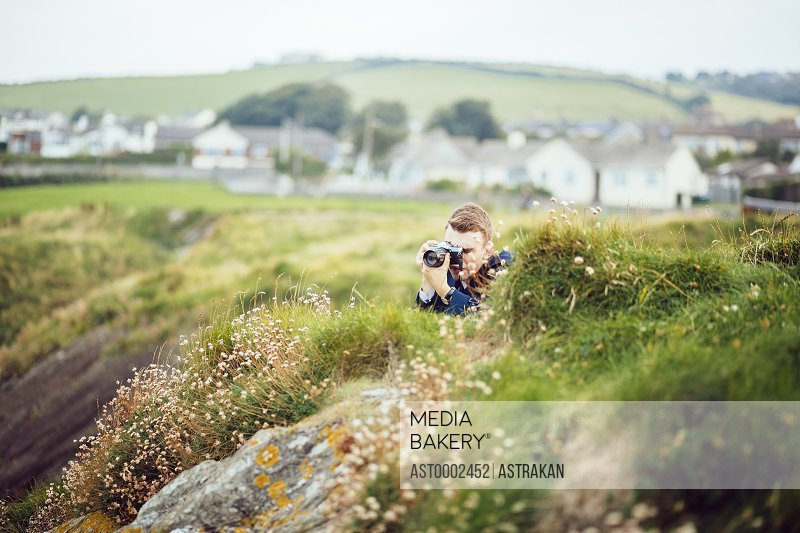 Man photographing on grassy hill