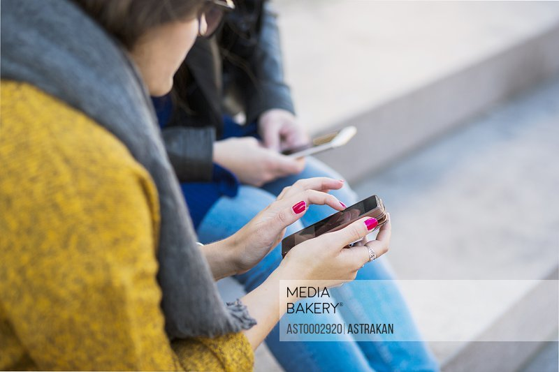 Close-up of women using smart phone while sitting on steps
