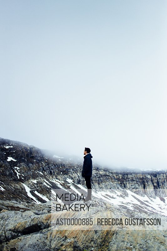 Full length side view of young man standing on rocky mountain during winter