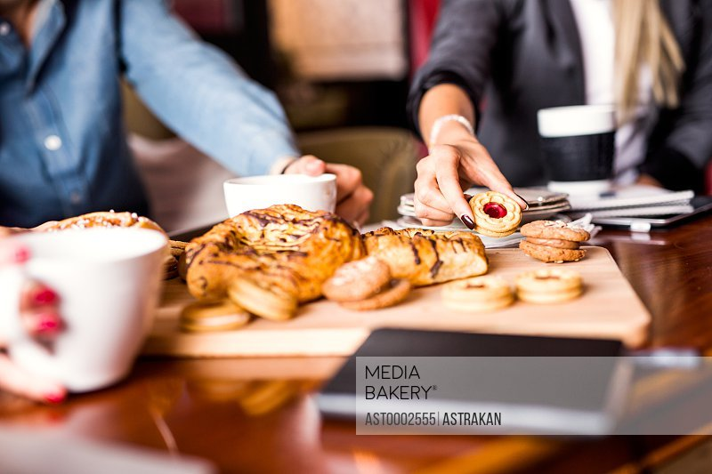 Midsection of business people having cookies at table in office
