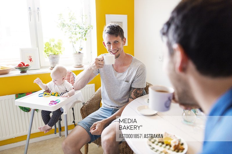 Gay men having coffee while baby girl playing on high chair at home