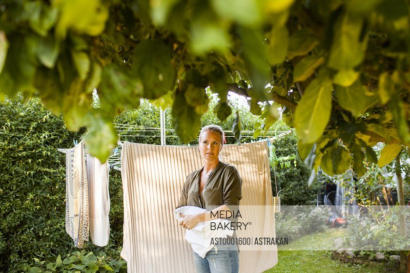 Thoughtful woman drying clothes in garden