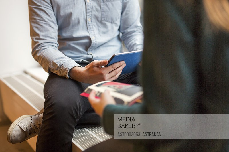 Midsection of business people with digital tablet and book in office