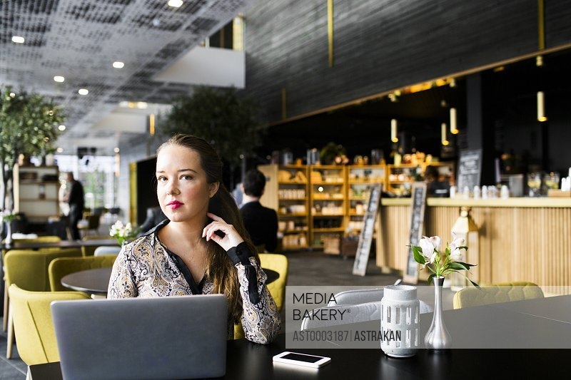 Confident businesswoman sitting at table with laptop in restaurant
