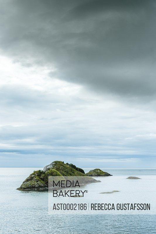 Mountain amidst sea against cloudy sky