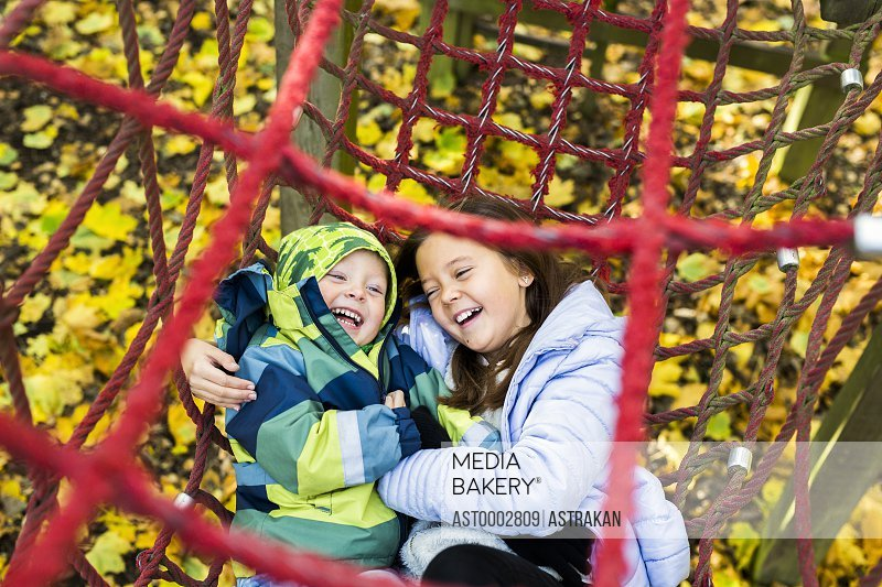 Playful brother and sisters sliding together in netting during obstacle course at forest