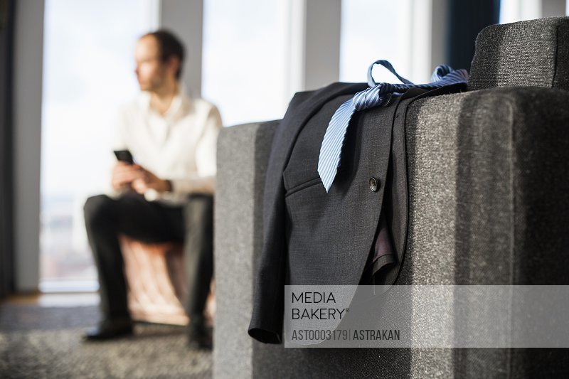 Suit and necktie on table while man sitting on bed at hotel room