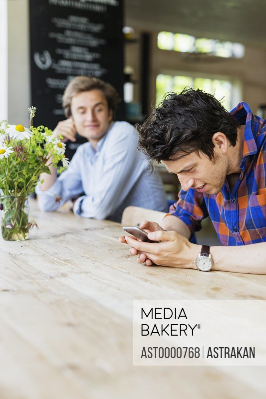 Man looking at friend using smart phone while sitting at cafe table