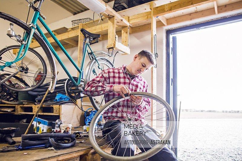Man repairing bicycle tire while sitting by doorway in workshop